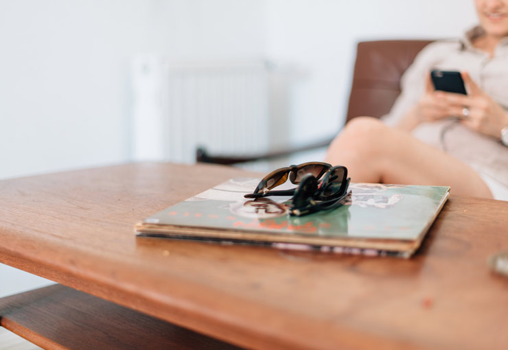 persona consultando el móvil al fondo, en primer plano dos pares de gafas de sol en la mesa